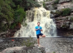 A day-tour companion performing yoga moves in front of a wet wonder.