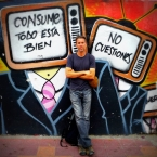 "Posing with quiteño street graffiti... I love the ironic anti-TV message: ""Consume! Everything's fine"" and ""Don't question"""
