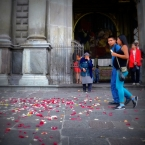 Passersby in front of San Francisco church strewn with rose petals after a wedding