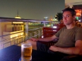 Enjoying a cold Bia Saigon on a rooftop terrace with fine evening views of HCMC