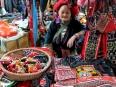 A red Dzao craftswoman in the market, they work busily creating beautiful sewing and needlework textiles